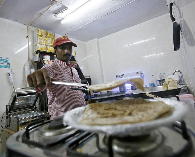 An inmate prepares food inside the kitchen of a restaurant run by the Tihar Jail authorities