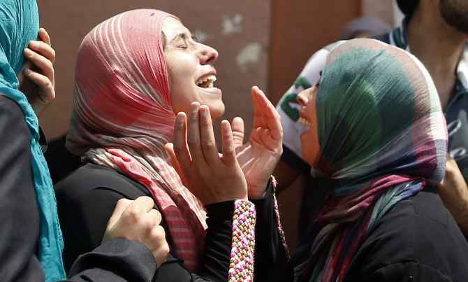 Palestinian women mourn the loss of a child killed in Israeli shelling in Gaza City.