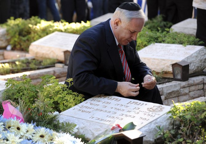 Israel's Prime Minister Benjamin Netanyahu lights a candle by his brother Yonatan's grave during a memorial ceremony for him at Mount Herzl military cemetery in Jerusalem