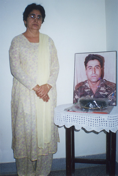 Kamal Batra with a picture of Vikram. His cap and the Indian flag that had wrapped his body is kept in front.