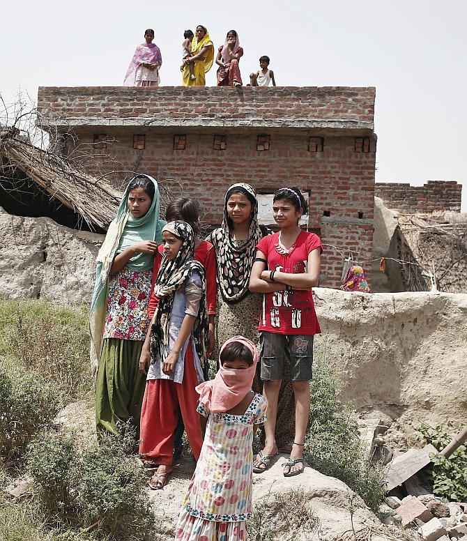 Villagers stand as they watch the house of one of the two teenage girls, who were raped and hanged from a tree, at Budaun district in UP
