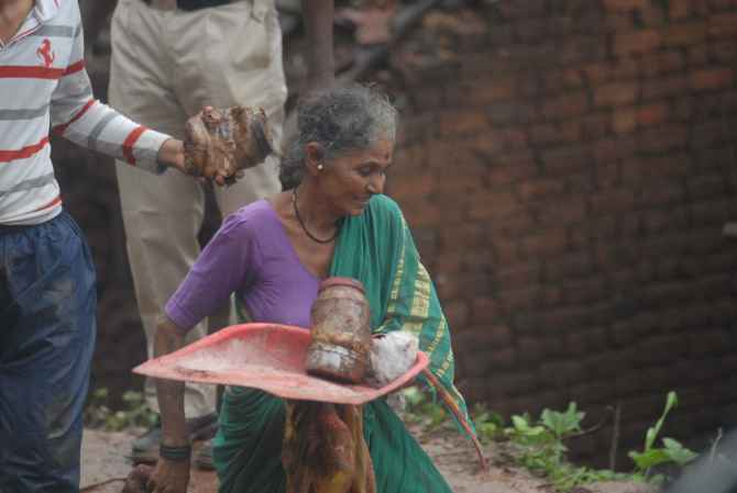 A woman, whose house was destroyed in the landslide, picks up her belongings