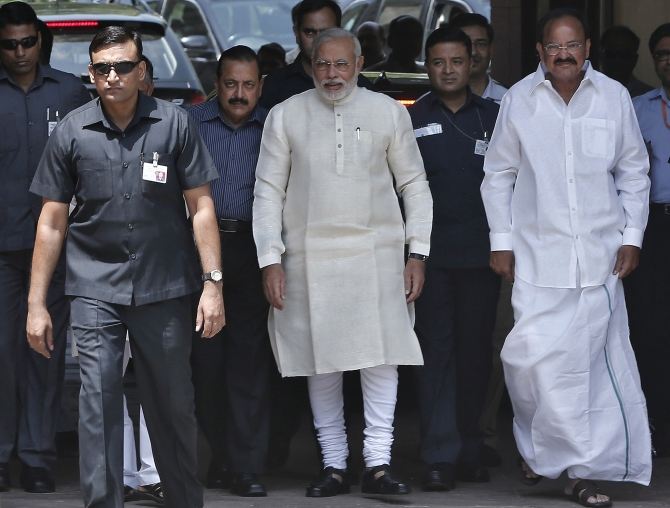 Prime Minister Narendra Modi walks with Parliamentary Affairs Minister Venkaiah Naidu to speak with the media in New Delhi.