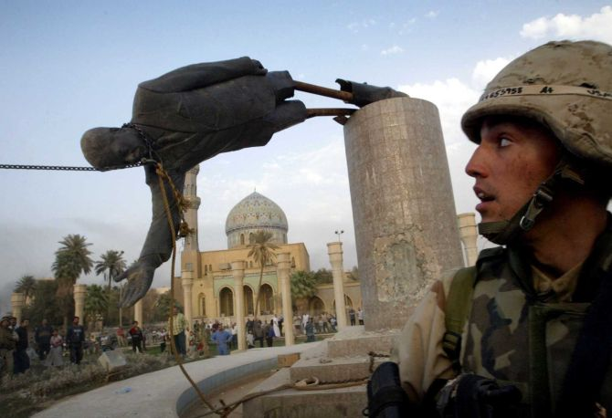 US Marine Corp watches as a statue of then Iraq's President Saddam Hussein falls in central Baghdad's Firdaus Square.