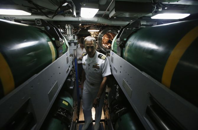 Commanding Officer Richard Rhinehart walks between rows of torpedoes in the torpedo room onboard the USS North Carolina (SSN-777) submarine docked at Changi Naval Base in Singapore