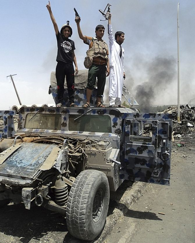 ISIS militants stand atop a car after they overtook Mosul.