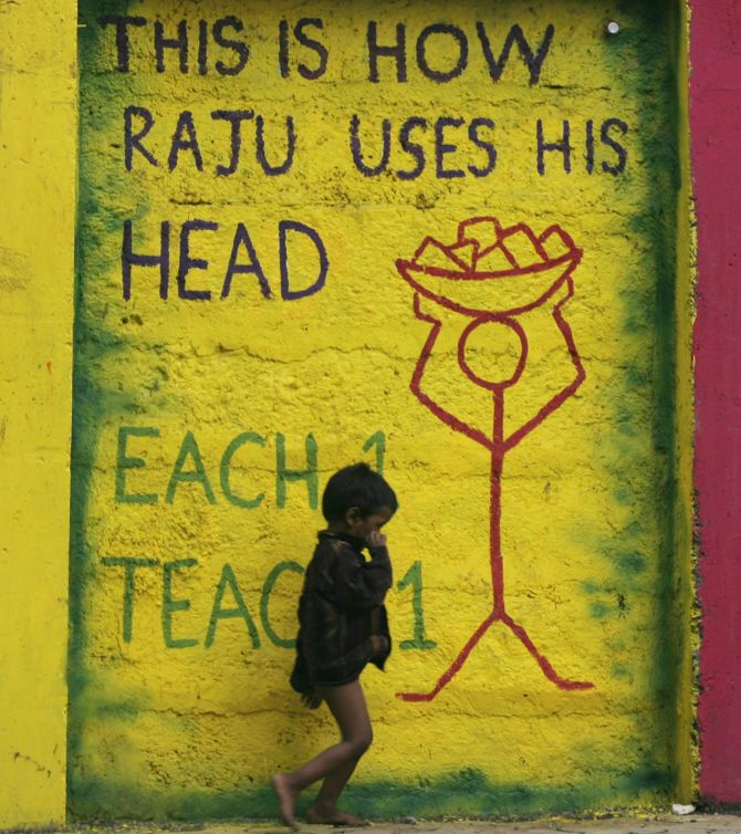 A child walks past graffiti on a street side wall in Mumbai.