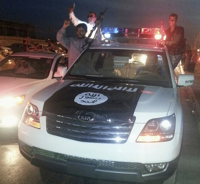 Fighters of the Islamic State of Iraq and the Levant celebrate on a police vehicle along a street in the city of Mosul, Iraq