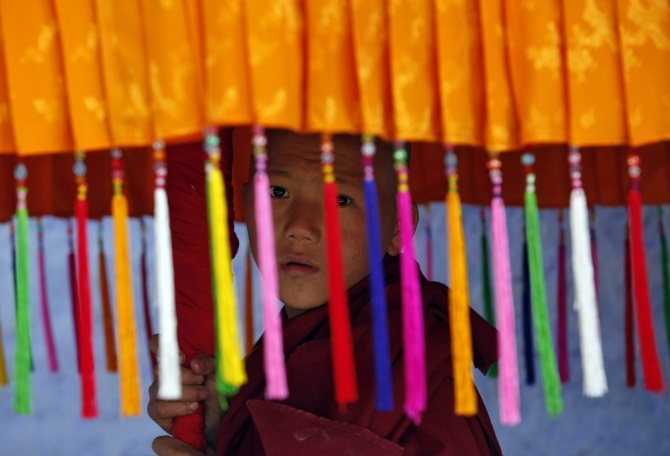 A young monk holds a traditional parasol as he waits for the arrival of the Dalai Lama in Pemayangtse monastery in Pelling, Sikkim