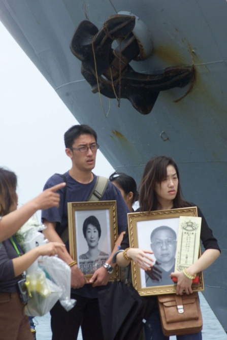 Relatives hold photos of loved ones who were aboard China Airlines flight CI 611 which crashed into the sea on Saturday prepare to board a Taiwan navy transportation ship, to make their way to a traditional spirit-calling ceremony near the island of Penghu.