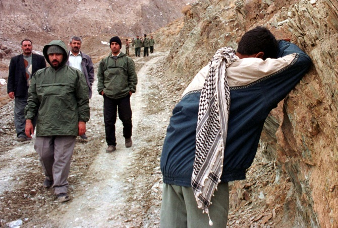 A Revolutionary Guard grieves over his dead c-orescue workers look on, on a near Kerman, in southeastern Iran.
