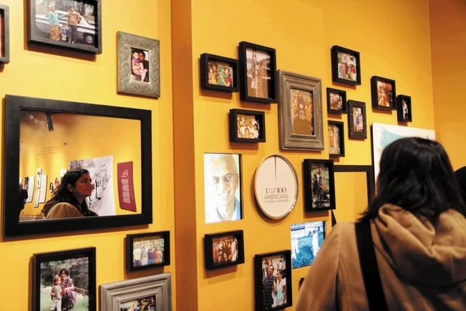 A wall of family photographs showing the diversity of the community.