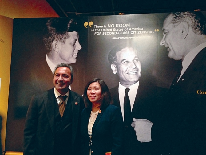US Representatives Ami Bera and Grace Meng pose against a photograph of US Congressman Dalip Singh Saund flanked by then Senators John F Kennedy and Lyndon Baines Johnson.