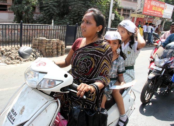 A mother with her two young daughters follow his convoy in Mumbai.