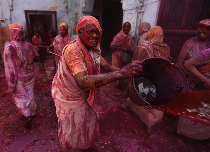 A widow throws coloured water during Holi celebrations at the ashram