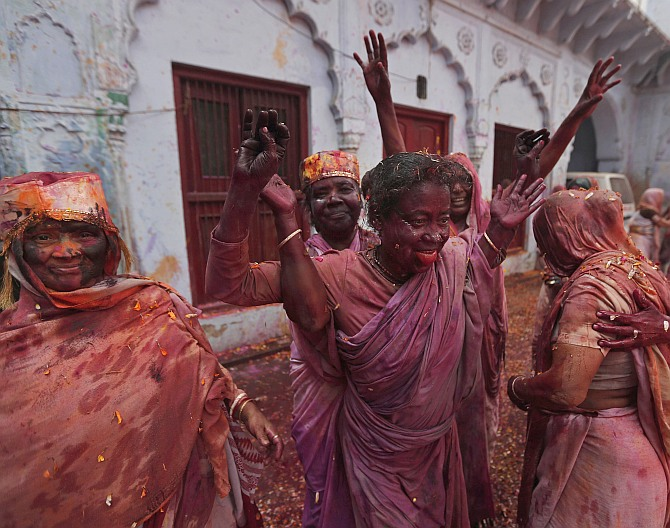 Widows dance as they take part in Holi celebrations at the ashram