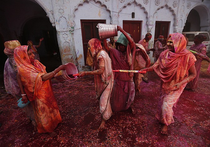 Widows spray coloured water on each other during Holi celebrations