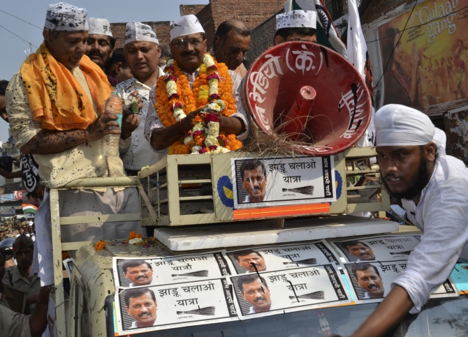 AAP leader Arvind Kejriwal stands atop a vehicle after ink was hurled at him and other party workers during a public rally in Varanasi