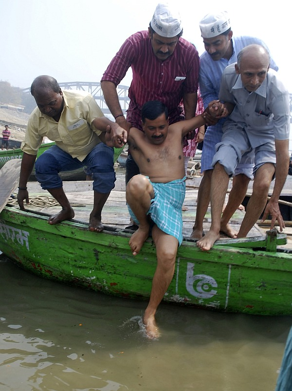 Arvind Kejriwal is helped by his party supporters as he prepares to take a dip in the waters of the Ganga after he arrived to attend a public rally ahead of the general elections in Varanasi