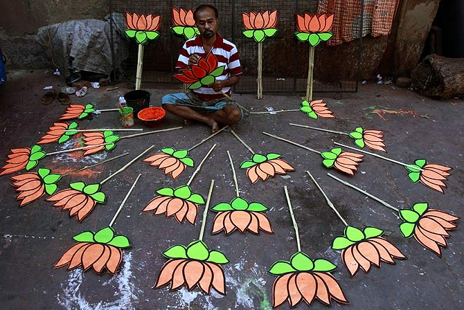 Kashinath Bagh paints cut-outs of lotuses, the BJP's party sumbol, at a workshop in Kolkata.