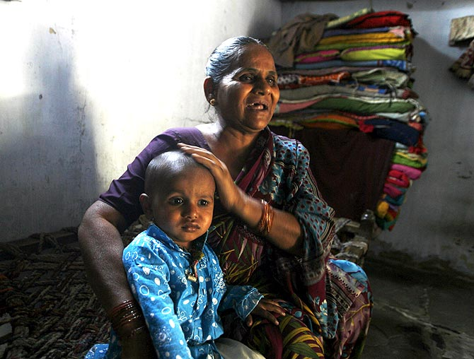 Hajira Sheikh, a riot survivor, with her grandson at her home in the rebuilt Naroda Patiya. Sheikh's invalid mother was burnt alive by a mob in the 2002 riots.