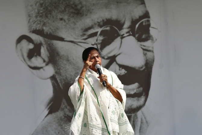 Mamata Banerjee, chief minister of West Bengal and Trinamool Congress chief, addresses her supporters in front of a portrait of Mahatma Gandhi during a rally ahead of the 2014 general elections, in New Delhi.