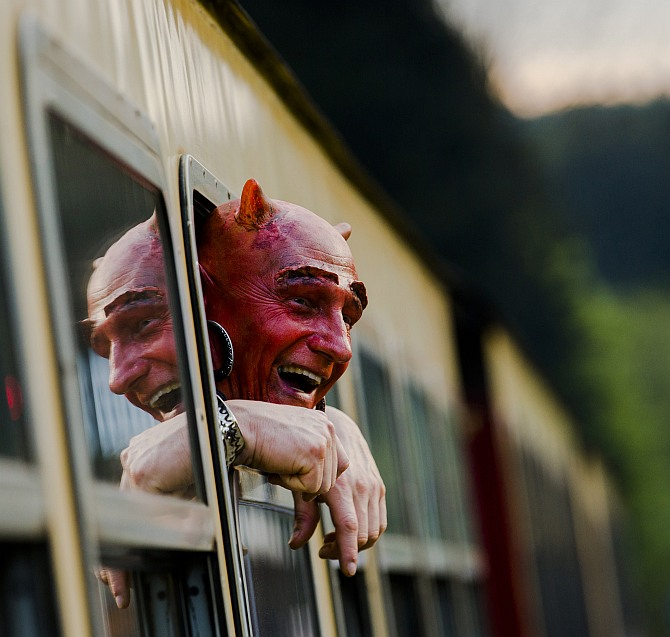 Man with a devil make-up looks out of a HSB light railway carriage as he travels through the Harz mountains to celebrate the Walpurgisnacht pagan festival