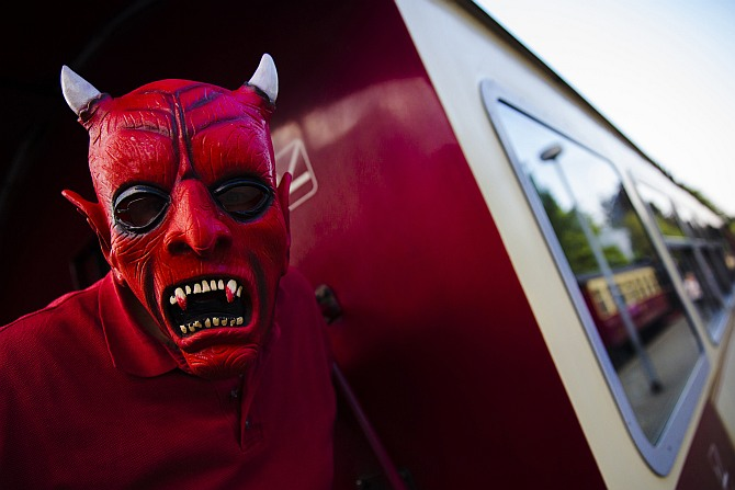 A man with devil make-up poses for a picture on a HSB light railway carriage travelling through the Harz mountains during celebrations marking the Walpurgisnacht pagan tradition