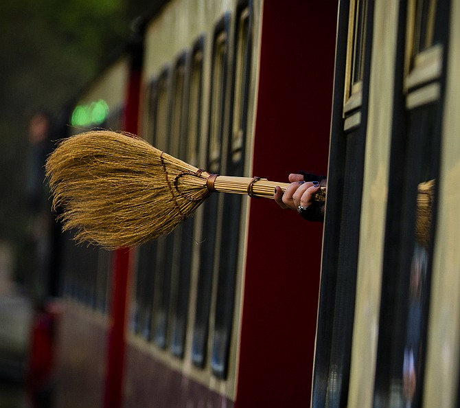 A woman holds a broom as she travels on the HSB light railway through the Harz mountains celebrating the Walpurgisnacht pagan festival