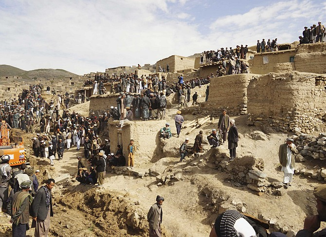 Afghan villagers gather at the site of the landslide at the Argo district in Badakhshan province