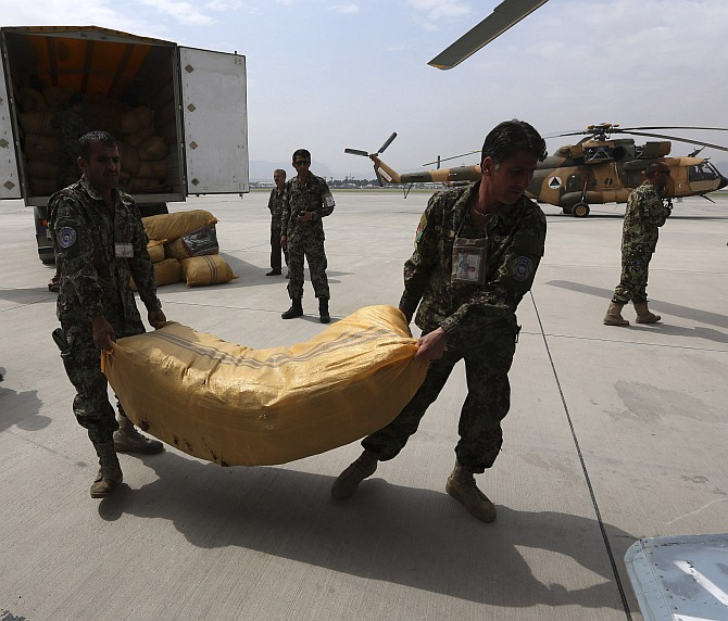 Afghan National Army troops load supply for survivors of the Badakhshan landslide onto a helicopter in Kabul