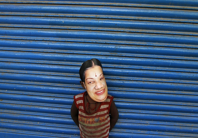 A boy wears a mask of Tamil Nadu CM J Jayalalithaa during a campaign in Chennai