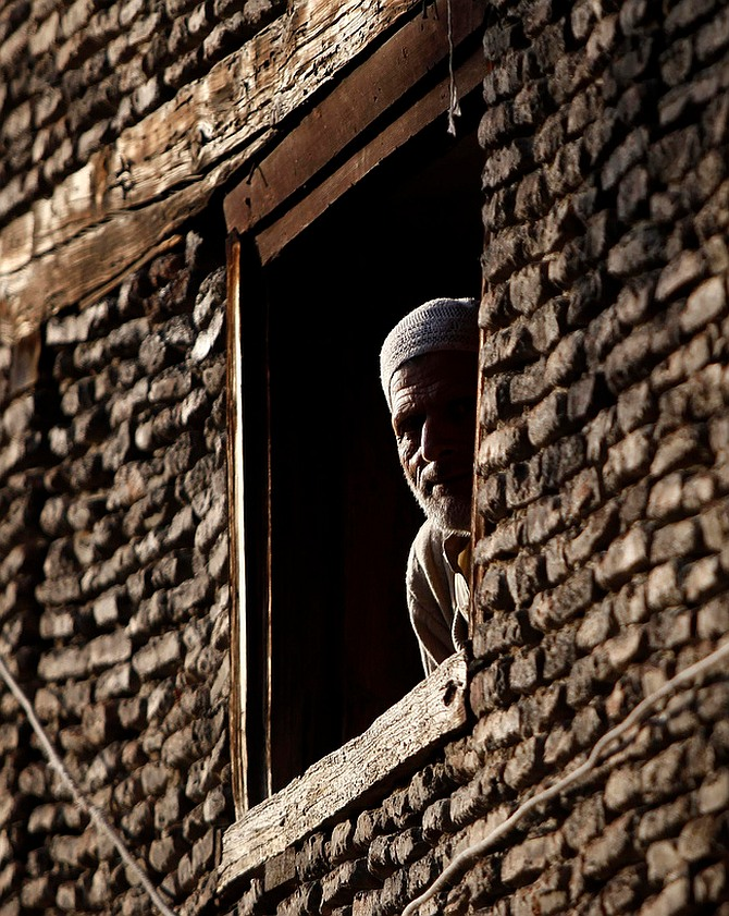 A Kashmiri man looks out of the window of his house