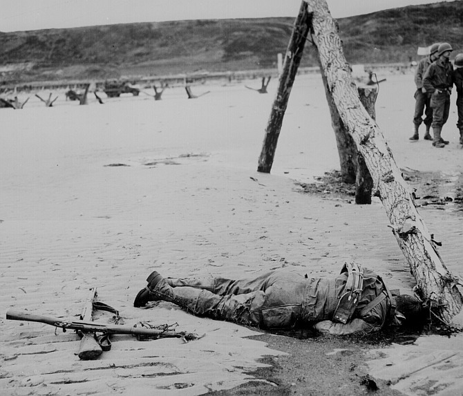 Crossed rifles lay in the sand as a comrade's tribute to a dead American soldier