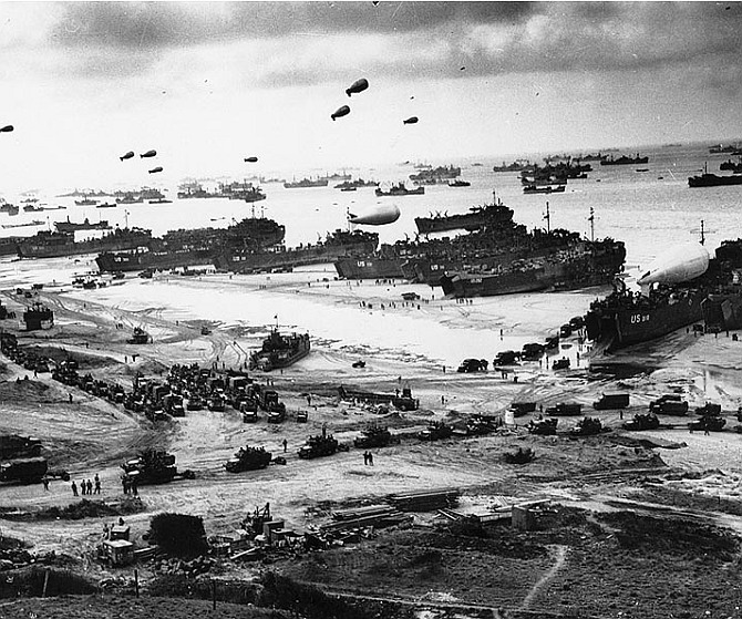 Landing ships putting cargo ashore on one of the invasion beaches, at low tide during the first days of the operation, June 1944. Among identifiable ships present are USS LST-532 (in the center of the view); USS LST-262 (3rd LST from right); USS LST-310 (2nd LST from right); USS LST-533 (partially visible at far right); and USS LST-524. Note barrage balloons overhead and Army half-track convoy forming up on the beach.