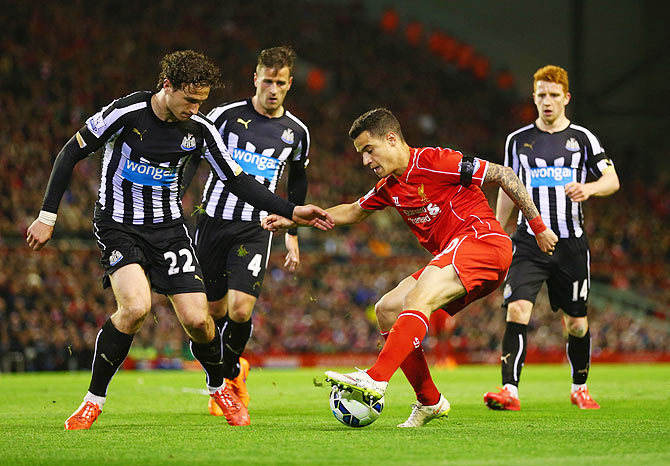 Liverpool's Philippe Coutinho dances past Newcastle defenders Ryan Taylor (4) Daryl Janmaat (22) and Jack Colback during their Premier League match at Anfield on Monday