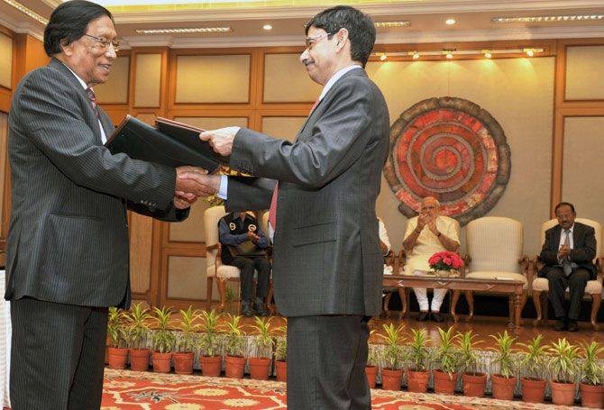 Thuingaleng Muivah, left, and R N Ravi, the Government of India's Special Interlocutor for the Naga talks, exchange copies of the agreement the NSCN-IM reached with the government, August 3.