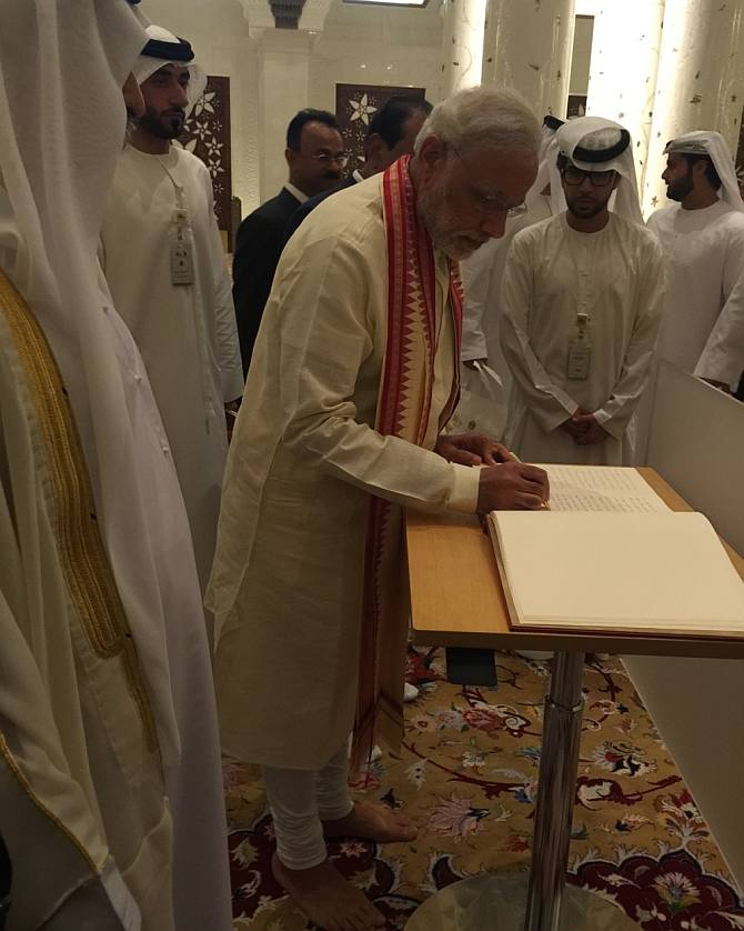 Indian Prime Minister Narendra Modi writing his comments in the visitors' book at the Sheikh Zayed Grand Mosque.