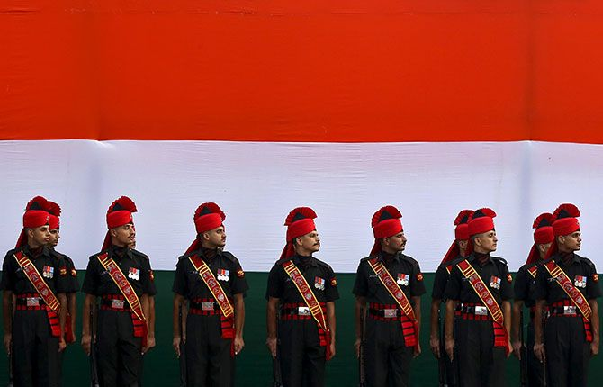 Indian soldiers stand guard in front of an India's national flag
