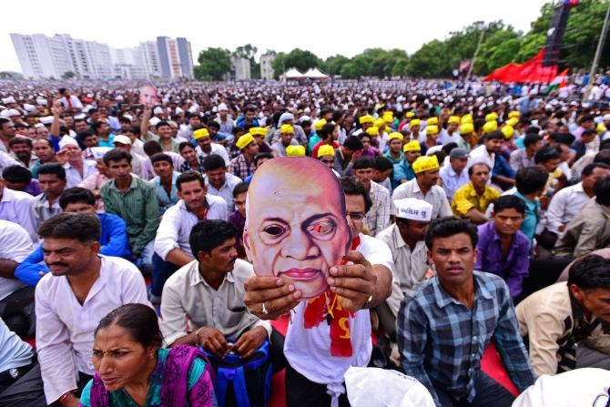 A youth displays a mask of Sardar Vallabhbhai Patel during the Kranti rally (revolution march) organised by the Patel ( Patidar) community to press their demands for reservation, at the GMDC Ground in Ahmedabad. Photograph: PTI Photo