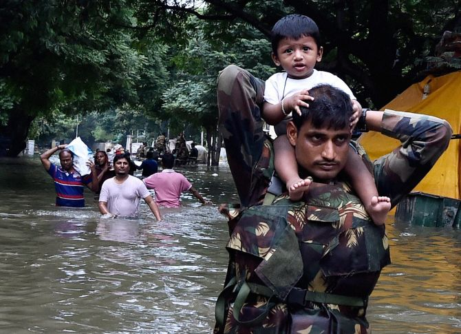 Army personnel carry children on their shoulders as they wade through flood waters in rain-hit Chennai on Thursday.