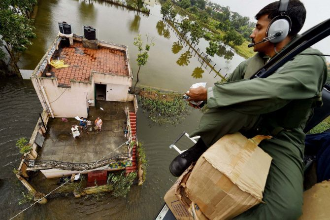 A Coast Guard helicopter drops relief material to residents stranded on a rooftop in Chennai. Photograph: R Senthil Kumar/PTI Photo
