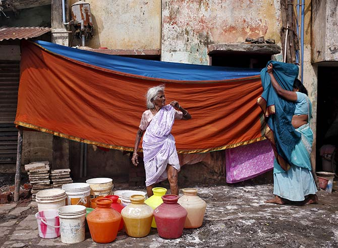 A woman waits outside her house for a water tanker to fill her containers with drinking water.