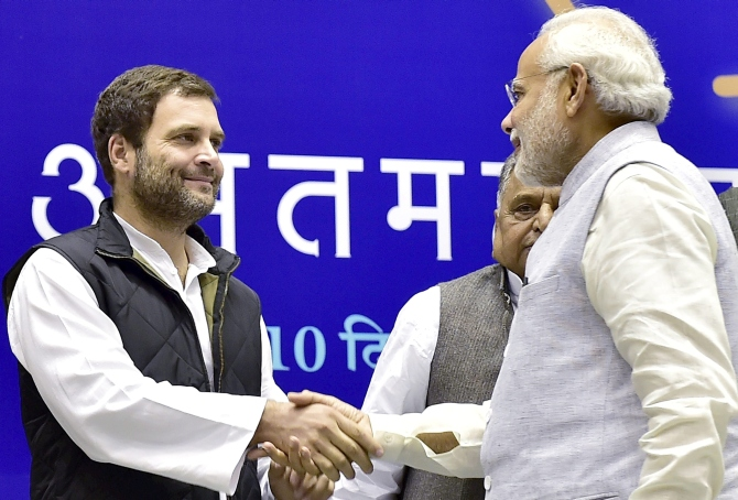 Prime Minister Narendra Damodardas Modi greets Congress President Rahul Gandhi as Samajwadi Party leader Mulayam Singh Yadav looks on