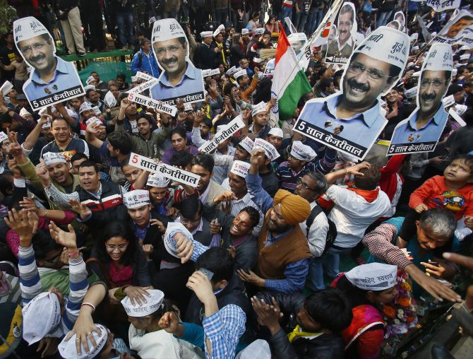 Aam Aadmi Party supporters with portraits of AAP leader Arvind Kejriwal, during celebrations outside the party office in New Delhi. Photograph: Anindito Mukherjee/Reuters