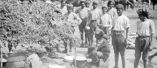 Indian soldiers wait for food at an improvised cookhouse at a camp near Querrieu in July 1916.