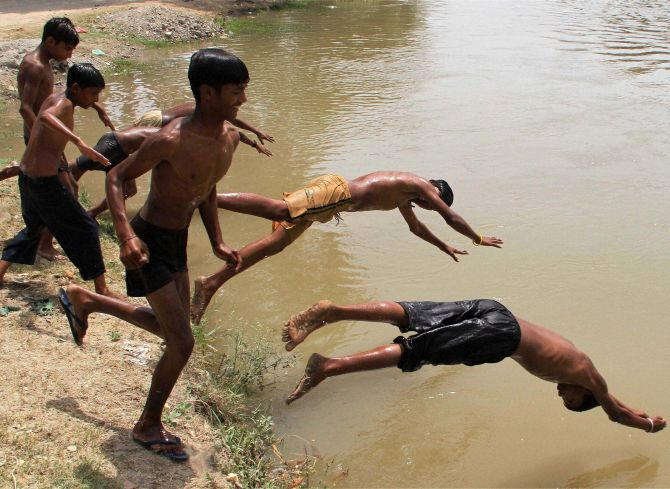 Children cool off in a canal in Bhatinda, Punjab