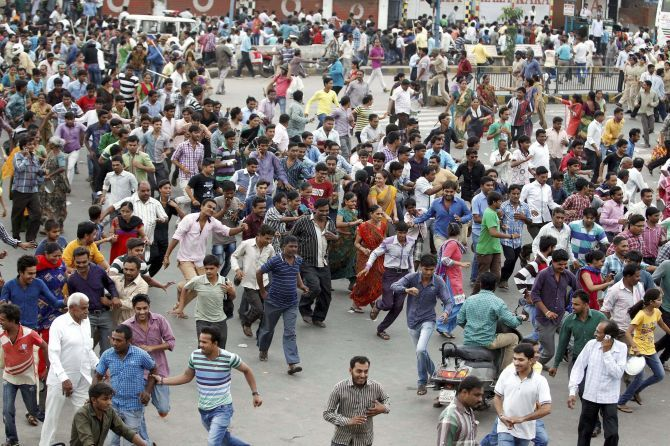 Patels run for cover after a police lathi charge to disperse crowds protesting against the arrest of their leader Hardik Patel. Photograph: PTI