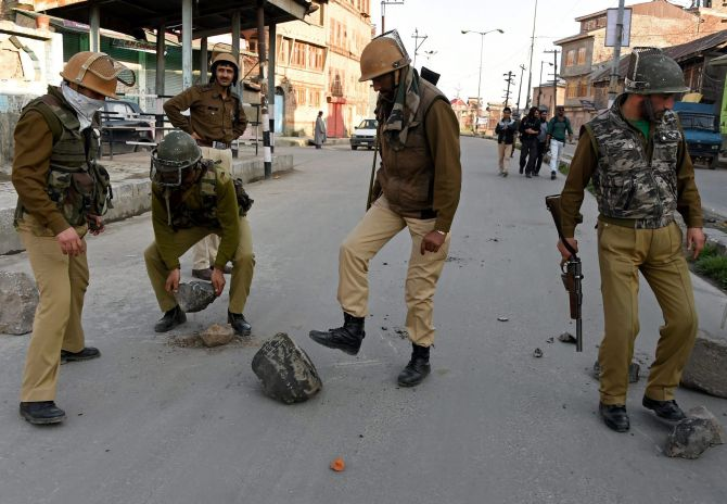 Security personnel remove a boulder from a deserted street after protests following the alleged molestation of a girl by a jawan. Photograph: S Irfan/PTI