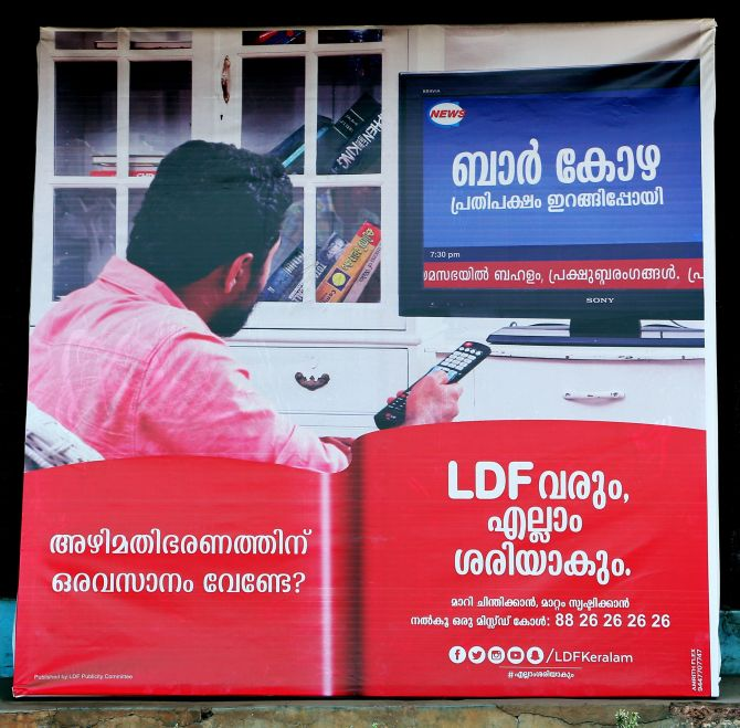 In this LDF election poster, a man with a remote in his hand watches a TV channel that talks about corruption on the shutting down bars in Kerala. Photograph: Sreeram Selvaraj
